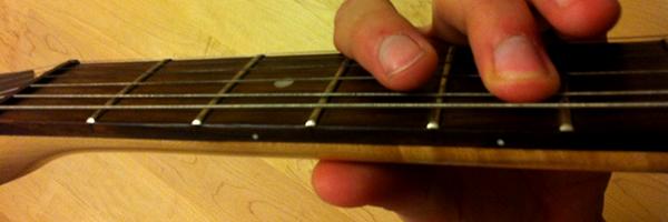 Mittelfinger im fünften Bund der Gitarre
